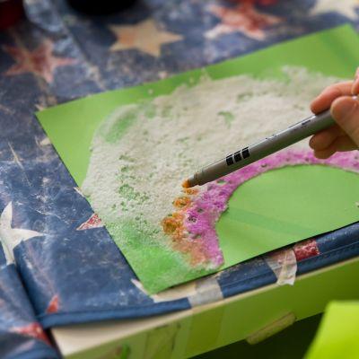 Lapsi värittää sateenkaarta paperille.