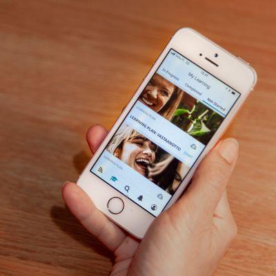 Puhelin, jonka näytöllä on Scandicin viestinnän ja perehdytyksen oppimissovellus.
