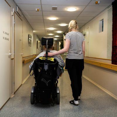 Hoitaja työntää pyörätuolissa istuvaa asiakasta hoitokodin käytävällä.