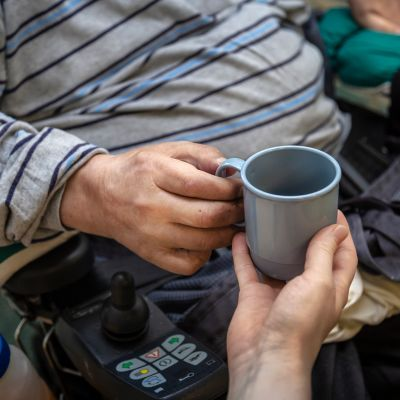 Hoitokodin hoitaja ojentaa kahvikupin asiakkaalle.