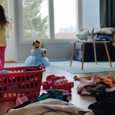 Två barn leker på vardagsrumsgolvet bredvid en hög sorterat byke. Det yngre barnet har en blå klänning på sig och gula underbyxor på huvudet.