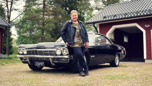 Mona Söderblom framför sin Cheva Impala 1966, en klassisk svart amerikansk bil