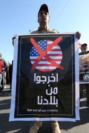 Lämna landet! kräver en demonstrant som tillhör en halvmilitär milisgrupp