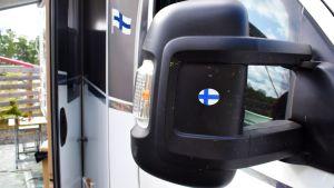 Backspegeln på en husbil med Finlands flagga påklistrad.