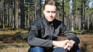 Emil Lindholm sitter på en stubbe.