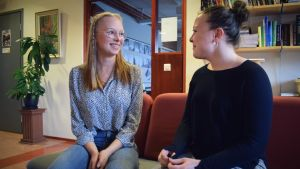 Gymnasieeleverna Hanna Gustafsson och Fanny Karell sitter i en soffa i skolkorridoren och talar med varandra.