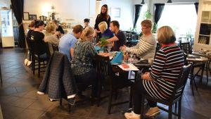 En grupp människor runt ett bord i caféet four-C i Dalsbruk.