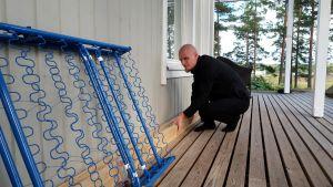 Richard Palonen lyfter på några bräder på husets terass.