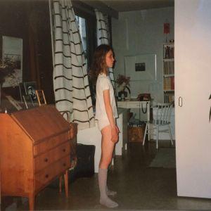 Teini-ikäinen langanlaiha tyttö seisoo kodin olohuoneessa yllään t-paita, pikkuhousut ja sukat.