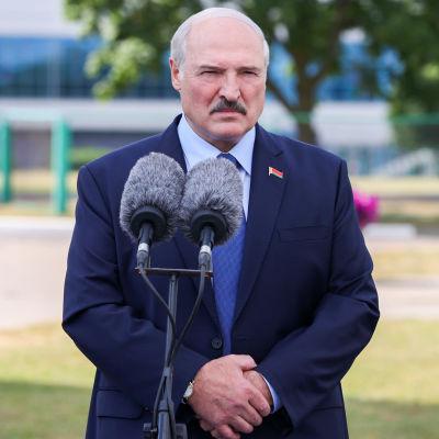 Aleksandr Lukasjenko framför mikrofoner då han talar efter röstning i val. Han har lite ljust, grått. Mörk mustasch och mörkblå kavaj. Ser sammanbiten ut.