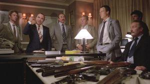 Harold (Bob Hoskins) puhuttelee muita gangstereita, etualalla pöytä täynnä erilaisia ampuma-aseita