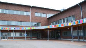 På bilden syns ett hus i rött tegel med flera fönster och dörrar i glas. På huset finns en bård med färggranna ränder och det står social- och hälsovårdscentral ovanför en av dörrarna.