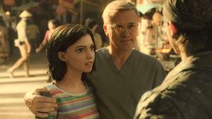 Doktor Ido står med armen beskyddande runt Alita.