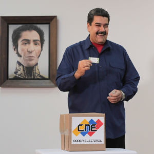 Nicolás Maduro lägger sin röst i söndagens lokalval, med ett porträtt på nationalhjälten Simón Bolívar i bakgrunden.