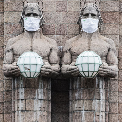 """I bild syns en skulptur """"Lyktbärare"""" utanför Helsingfors tågstation som bär munskydd."""