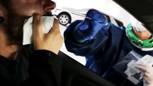 Sjukskötare i skyddsmundering sträcker in en provtagningssticka genom bilfönstret. En man med nerdraget munskydd blir coronatestad.