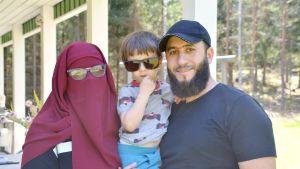 Pernilla Sjögård i vinröd burka och med glasögon på och Abdul Aki i svart t-skjorta och keps håller i sin son Adam Aki i grå tröija med bilar på och solglasögon på.