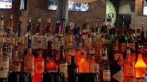 Stort urval alkoholflaskor på Mercury bar i skum belysning.