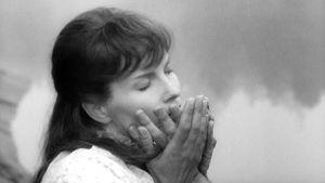 Nainen painaa rakastettunsa käden kasvojaan vasten. Kuva elokuvasta Rakastavia pareja.