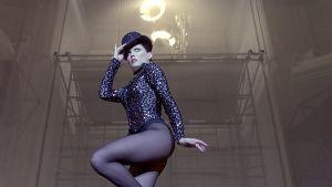 Tanssija kimaltavassa asussa ja knallihatussa elokuvassa Syke ei sammu (All That Jazz)