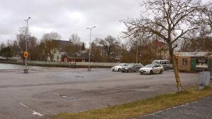En astfaltplan med fyra bilar på, i ena hörnet ser man lilla taxihuset.