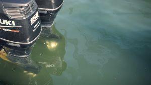 Två motorer i vattnet, lite bensin flyter på ytan.