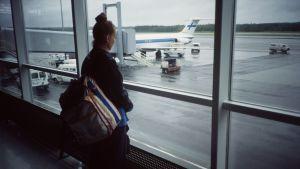 Ung kvinna tittar ut genom fönstret på flygfältets landningsbana.