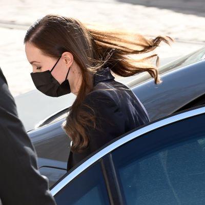 Statsminister Sanna Marin stiger ur baksätet på en bil. En man håller upp dörren åt henne.