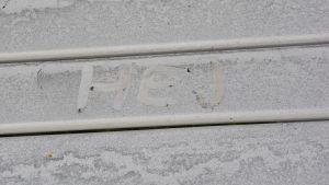 Någon har skrivit ett hej i dammet på en vit bänk.