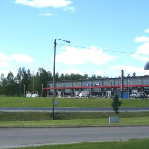 På bilden syns två vägar som har gräs på båda sidor. I bakgrunden syns en affärsfastighet.