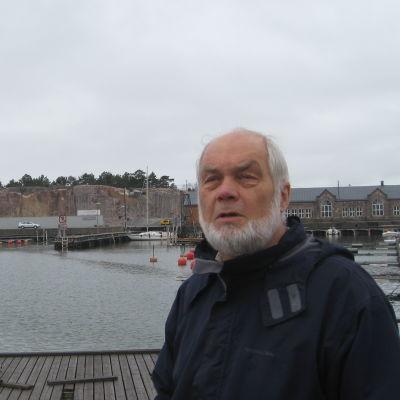 En man med skägg vid en strand. Han heter Yrjö Sahlstedt.