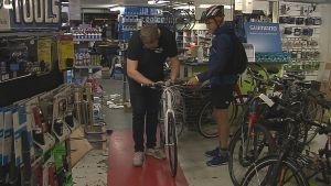 Cykelförsäljare fixar på en cykel medan kunden med cykelhjälm väntar.