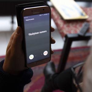 """Äldre kvinna tittar på sin telefon som ringer. På skärmen står """"yksityinen numero"""" det vill säga """"privat nummer""""."""