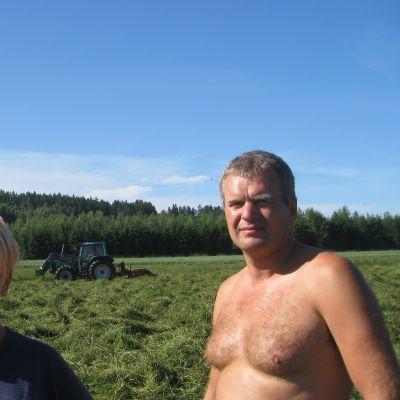 Jordbrukarna Johanna och Anders Wasström i Broby, Raseborg, I bakgrunden en traktor som fäller hö.