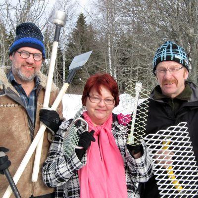 Nainen ja kaksi miestä työkaluja käsissään