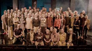 Ryhmäteatterilaisia ryhmäkuvassa lavalla. Kuva Mika Kaurismäen ohjaamasta dokumenttielokuvasta Ryhmäteatteri (2018).