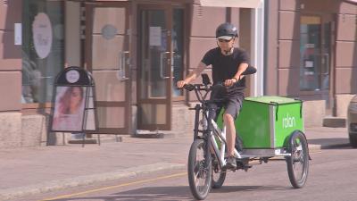 Ett cykelbud med svart hjälm kommer cyklande med en stor grön transportlåda bakpå cykeln.