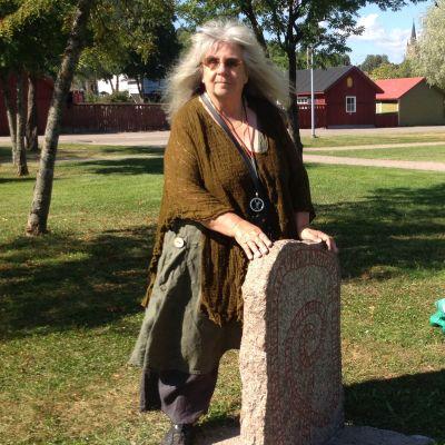 Nainen seisoo riimukiven takana rantapuistossa.