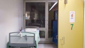 Kirurgisen osaston käytävä, jossa näkyy tyhjä potilassänky.