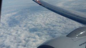Bild tagen ut från flygplansfönster med vinge, motor och moln.