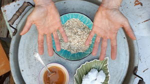 Putaat kädet ja kolme kulhoa: hunajaa, kaurahiutaleita ja kookosrasvaa