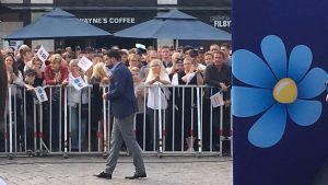 Jimmie Åkesson talar och mycket folk med SD-flaggor bakom ett kravallstaket.