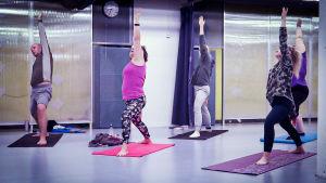 Riikka och fyra andra personer är i yogasalen. Det står på sina mattor i krigarpostion.