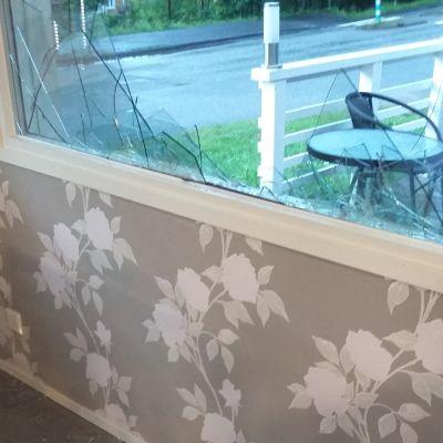 Ett fönster som söndrats. Glassplitter ligger på golvet.