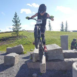 Pojke cyklar på en sten vid en grusplan.