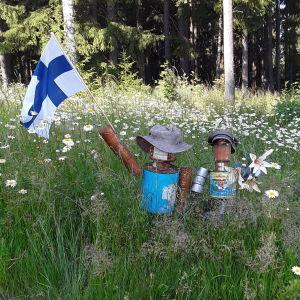 Kaksi peltiämpäreistä ja tölkeistä tehtyä hahmoa heinikossa. Toinen hahmoista tervehtii ohikulkijaa Suomen lippu kädessä.