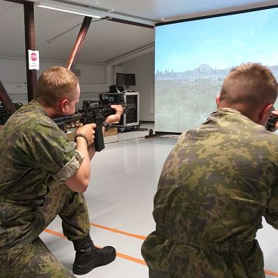 Varusmiehet harjoittelevat ampumista simulaattorissa.