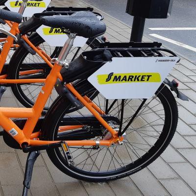Flera orange stadscyklar på rad som folk kan hyra.