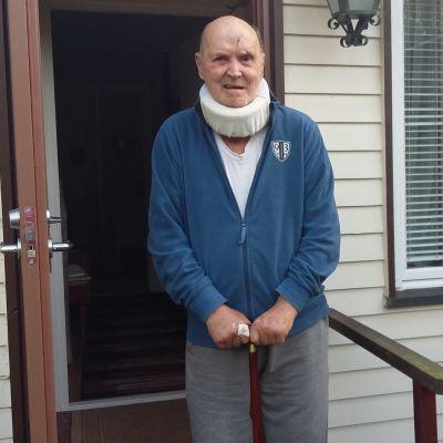 En äldre man med nackstöd och sår i pannan står på en trappa utanför ett vitt hus i trä.