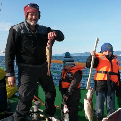 Anton Trøen yhdessä hänen ja Priitan poikien kanssa. Kaikilla kädessä turska ja taustalla näkyy sininen meri.